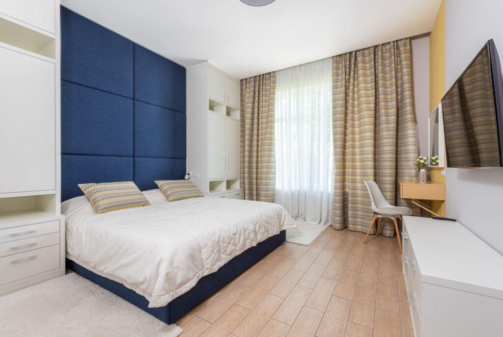 paragraf 1. -Dormitor in stil scandinav (38)-minAmenajările interioare în stil scandinav încep de la culoarea pereților. Albul este predominant, fiind uneori înlocuit sau combinat cu diverse nuanțe de gri scandinav. Aceste culori sunt asociate cu lemnul, care trebuie să fie și el în nuanțe deschise, lăsat natural sau vopsit. În stilul scandinav se merge pe culori mate, dar extrem de luminoase.  Albul și griul scandinav se combină cu roz, albastru, galben și uneori chiar verde. Aceste pete de culoare sunt în nuanțe deschise și mate, dând senzația de suprafață prăfuită, dar în același timp luminoasă.  Pe lângă culori, o altă caracteristică definitorie a stilului de amenajare interioară din țările nordice este utilizarea elementelor de mobilier din lemn masiv. Indiferent că este vorba despre un simplu scaun sau despre pat, totul trebuie să arate solid, greu. Îmbinarea albului cu diverse nuanțe de lemn este esențială.
